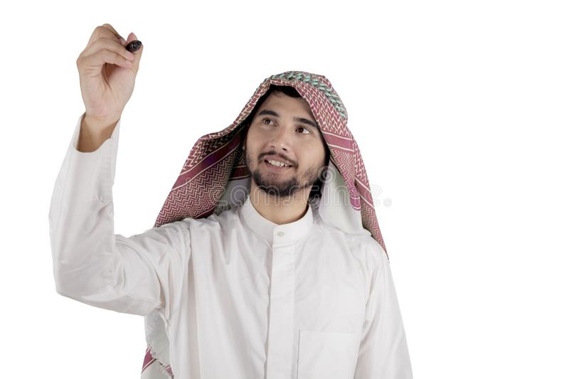 Arabian entrepreneur writing on the whiteboard. Picture of male entrepreneur wearing Islamic clothes while writing on the whiteboard, isolated white background royalty free stock photos