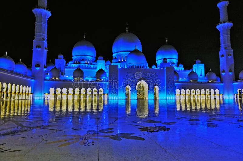 Arabian fairy tale. The magnificent mosque at night. Domes and minarets are highlighted in blue. Inside is a bright golden light. On a perfectly smooth floor royalty free stock image