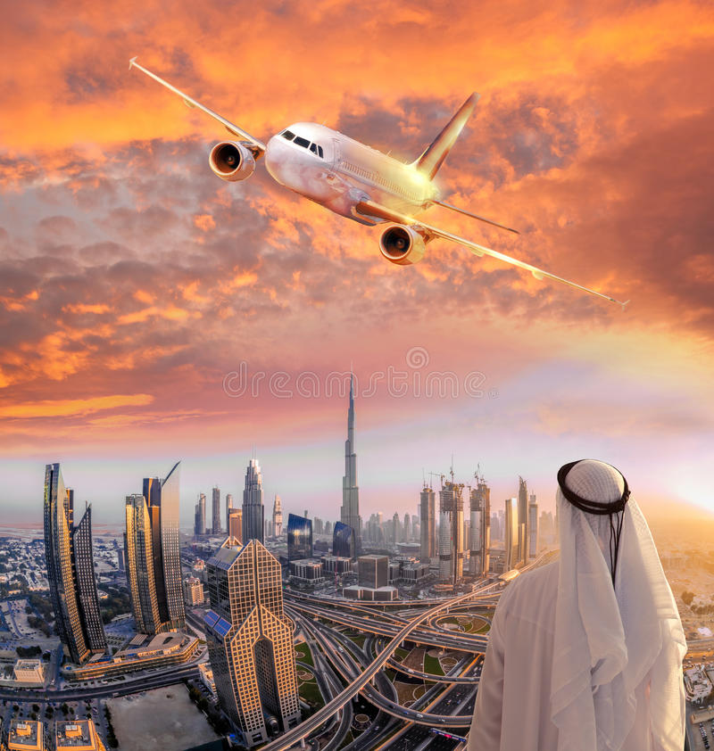 Arabian man with airplane flying over Dubai against colorful sunset in United Arab Emirates. Arabian man with airplane flying over famous Dubai against colorful stock image