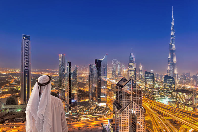 Arabian Man Watching Night Cityscape Of Dubai With Modern Futuristic Architecture In United Arab Emirates Stock Photo - Image of east, hotel: 121393770