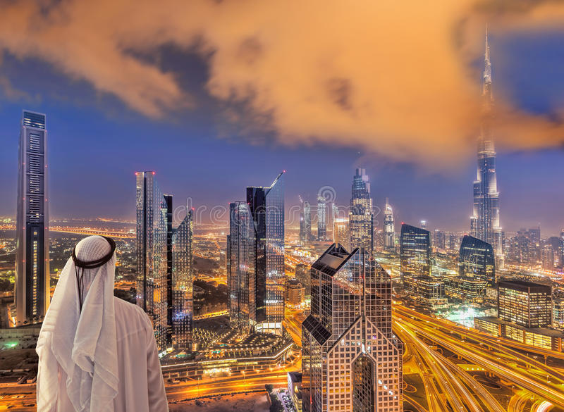 Arabian man watching night cityscape of Dubai with modern futuristic architecture in United Arab Emirates. Arabian man watching night cityscape of famous Dubai royalty free stock image