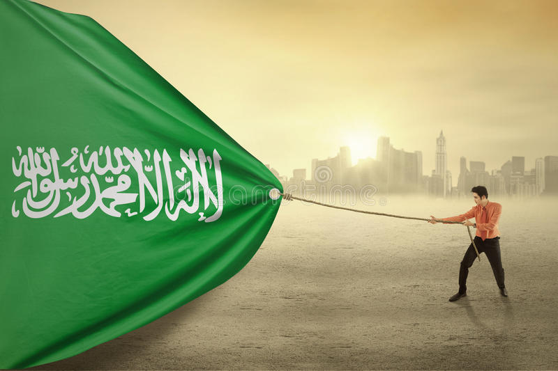 Arabian person dragging flag of Saudi Arabia. Image of young businessman pulling a flag of Saudi Arabia, shot outdoors royalty free stock image