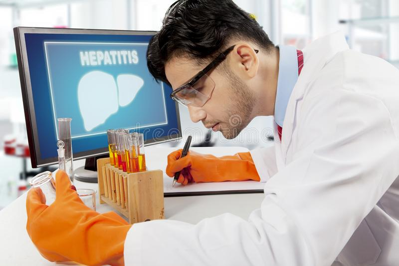 Arabian scientist with liver symbol on computer. Arabian scientist looking at test tube and writing on the clipboard with liver symbol on computer screen stock image