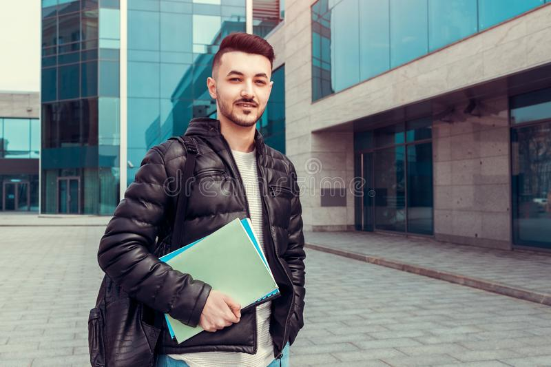 Arabian student holding copybooks by modern university outside. Young man with backpack looking at camera royalty free stock photos