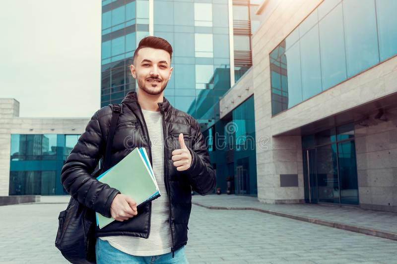 Arabian student showing thumb up holding copybooks by modern university. Happy young man successful in education. royalty free stock image