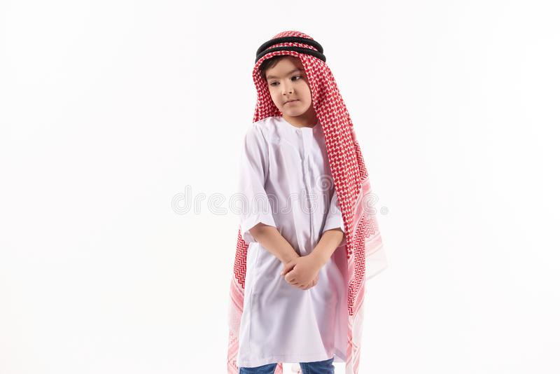 Arabian thoughtful boy in keffiyeh is standing. With hands folded. Isolated on white background. Studio portrait royalty free stock photo