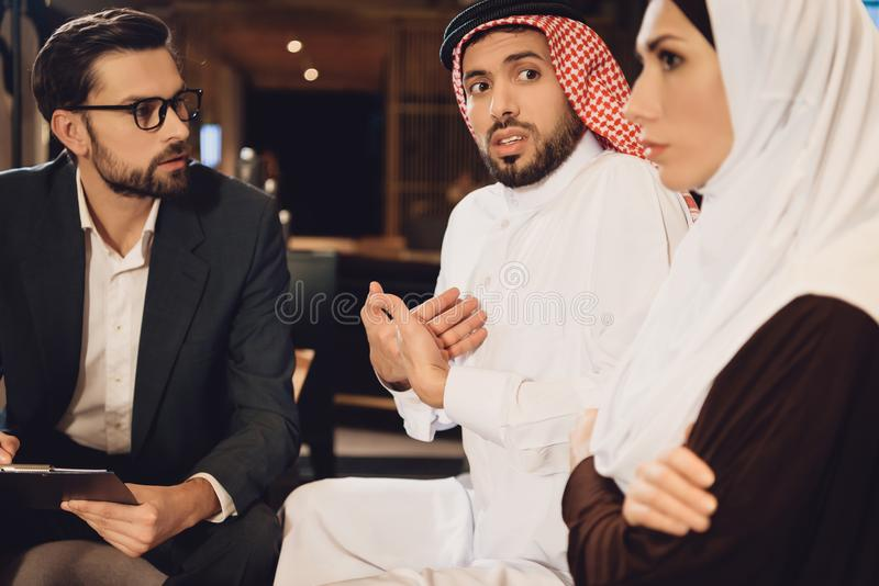 Arabian wife resent on husband at reception. Of therapist. Discussion of family problems in office of psychologist royalty free stock image