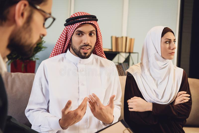 Arabian wife resent on husband at reception. Of therapist. Discussion of family problems in office of psychologist royalty free stock photos