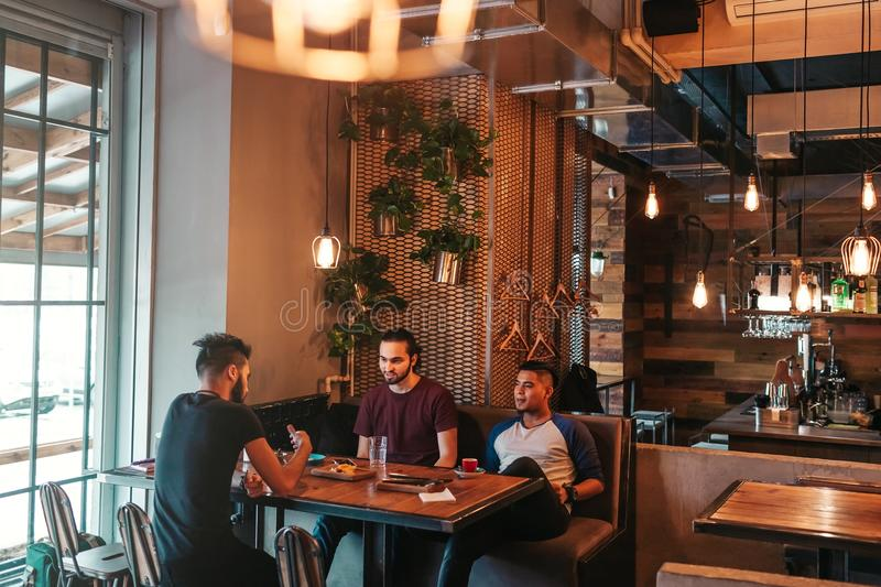 Arabian young men hanging in loft cafe. Group of mixed race people talking in lounge bar and having drinks. Friends chilling out and relaxing stock images