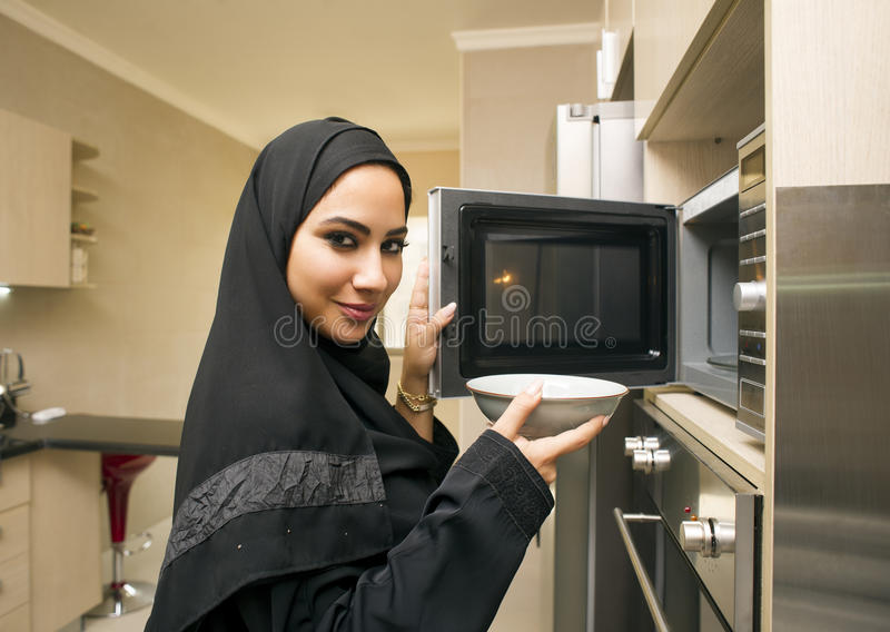 Arabian young woman in kitchen using microwave oven stock images