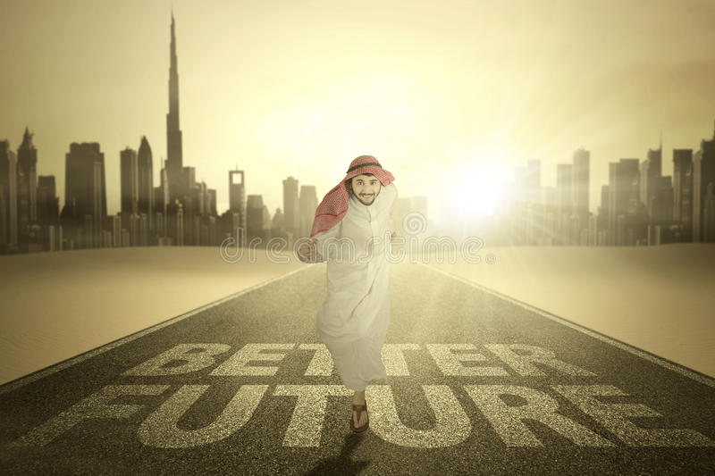 Arabic businessman runs with Better Future word. Arabic young businessman running on the highway with Better Future word and bright sunlight stock images