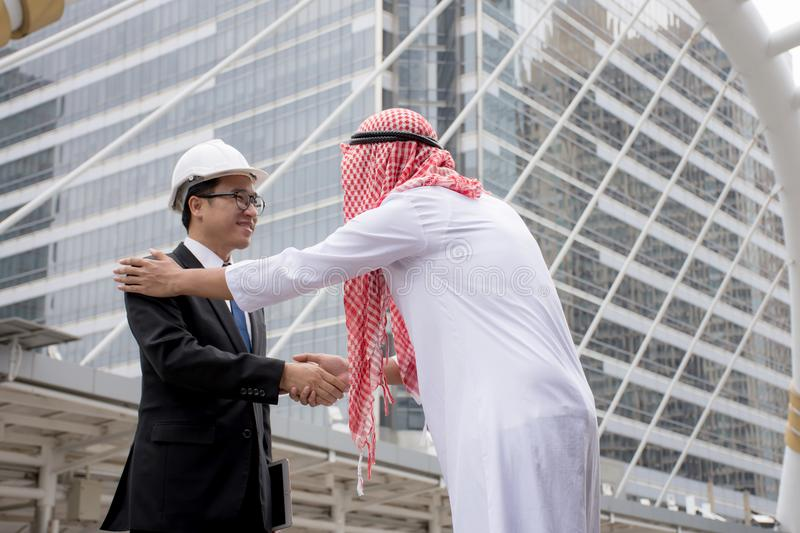 Arabic businessman shaking hands Asian Engineering over a deal negotiation to success stock photo