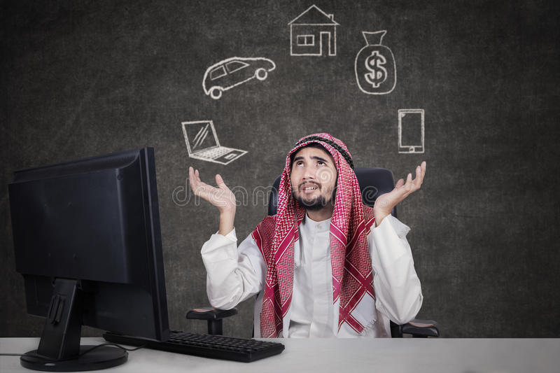 Arabic businessman thinking his dreams. Arabic young businessman working with computer while wearing traditional clothes and thinking his dreams royalty free stock photography