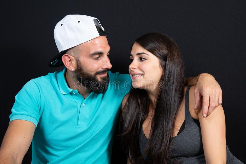 Arabic couple man with bearded and cap with pretty woman beauty arab in lifestyle over black background stock photography