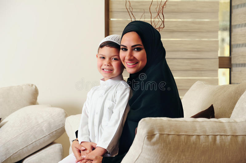 Arabic family, mother and son sitting on the couch in their living room royalty free stock images