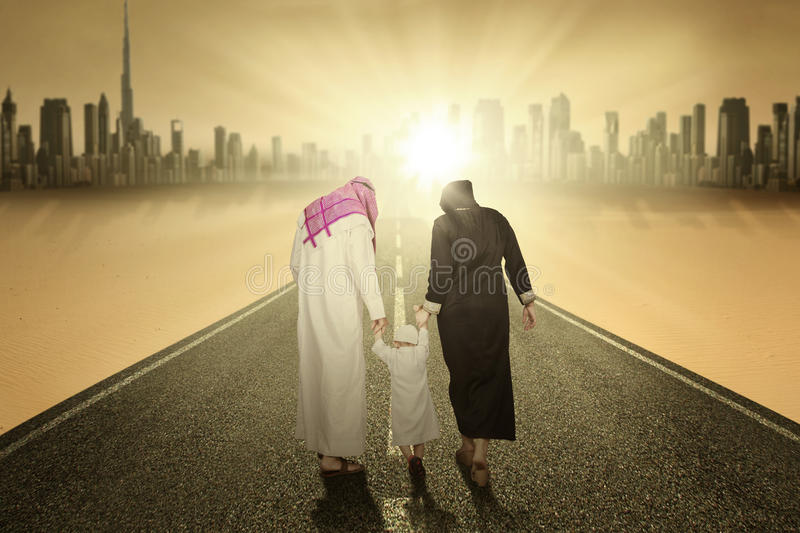 Arabic family walking on the highway. Rear view of arabic family walking on the highway while holding hands stock images