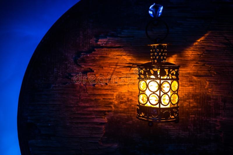 Arabic lantern with candle at night for Islamic holiday. Muslim holy month Ramadan. The end of Eid and Happy New Year. Copy space on dark background stock images