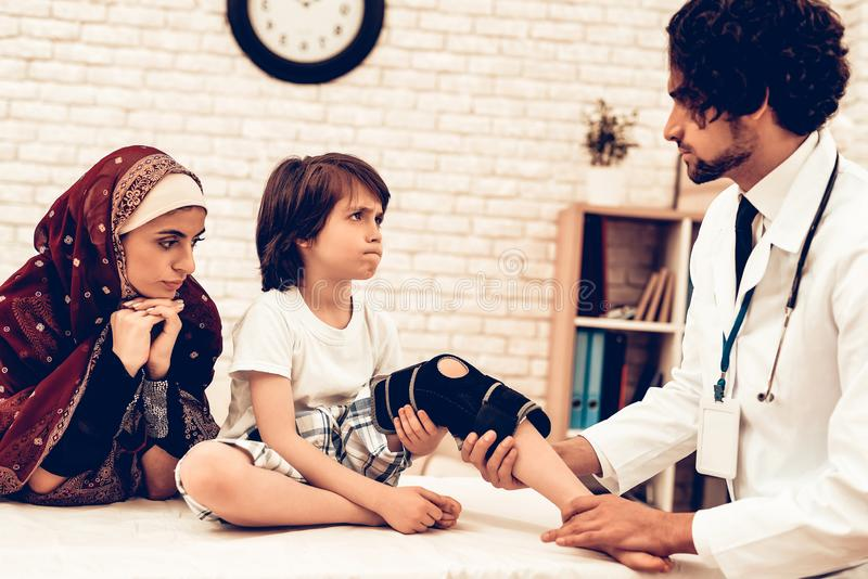 Arabic Male Doctor Bandaging Leg Injury of Child. Hospital Concept. Healthy Concept. Child Patient Visiting Doctor. Doctor royalty free stock photos