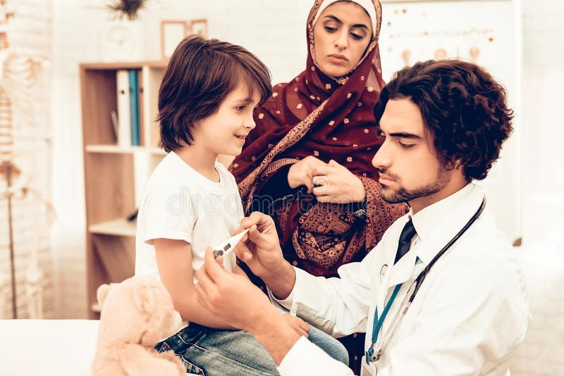 Arabic Male Doctor Examining Measuring Temperature. Child at the Pediatrician. Hospital Concept. Healthy Concept. Child Patient Visiting Doctor. Doctor royalty free stock photo