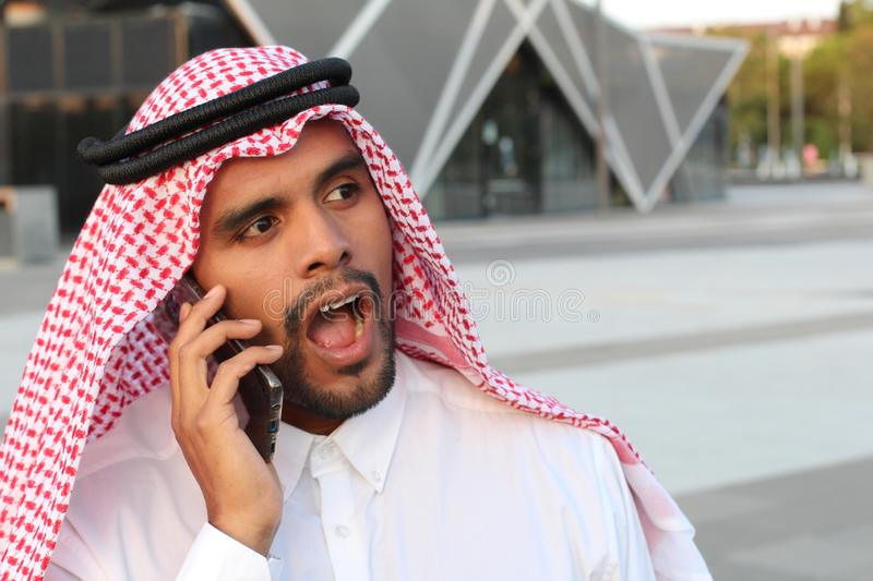 Arabic man in disbelief during business call royalty free stock images