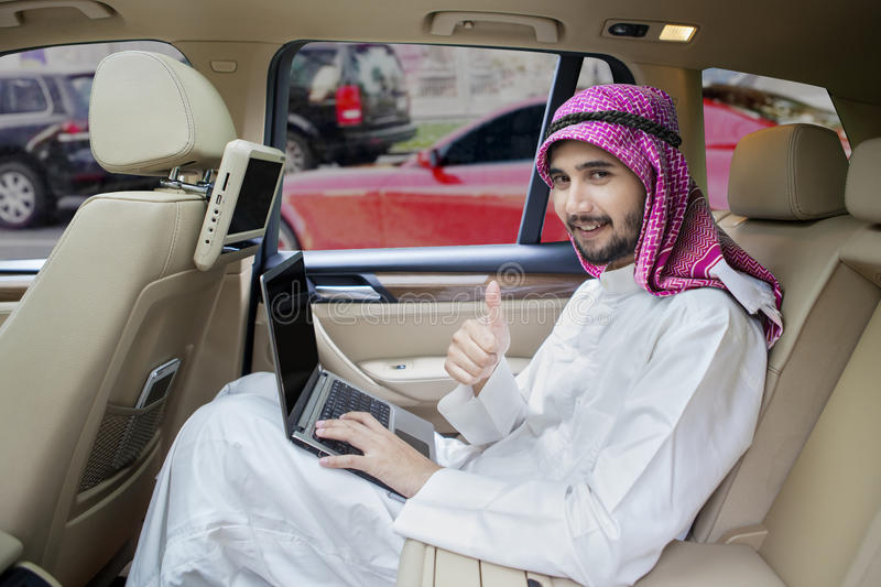 Arabic man with laptop shows OK sign. Arabic young businessman showing thumb up while using a laptop computer in the car stock photography