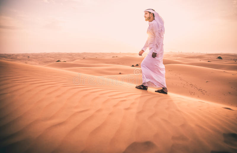 Arabic man with traditional emirates clothes walking in the desert royalty free stock images