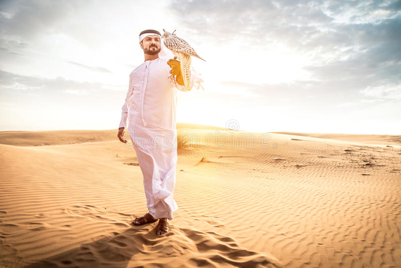 Arabic man with traditional emirates clothes walking in the desert with his falcon bird royalty free stock image