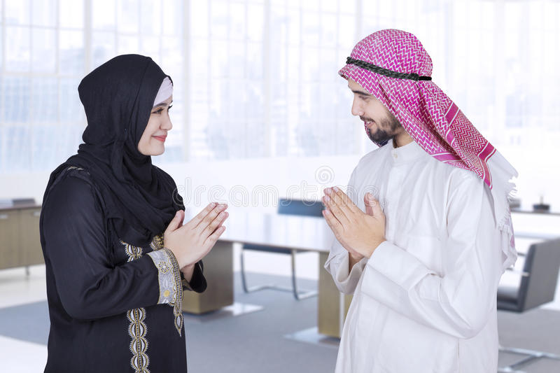 Arabic people give a salute in office. Two Arabic businesspeople give a salute to each other in the office room royalty free stock images