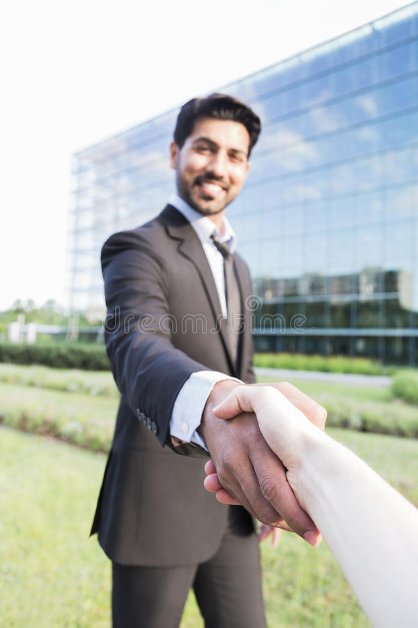 Successful arabic businessman or worker shaking hands with person. Arabic serious smiling happy successful positive businessman or worker in black suit with stock photo