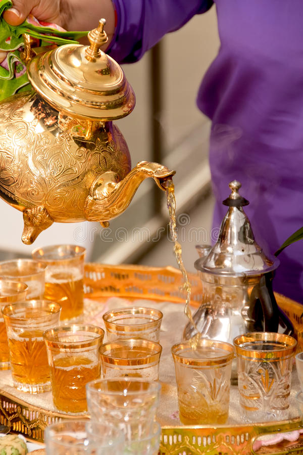 Arabic tea served in a golden teapot stock photography