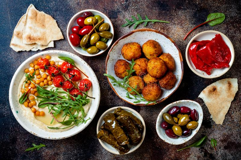 Arabic traditional cuisine. Middle Eastern meze with pita, olives, hummus, stuffed dolma, falafel balls, pickles. royalty free stock photos
