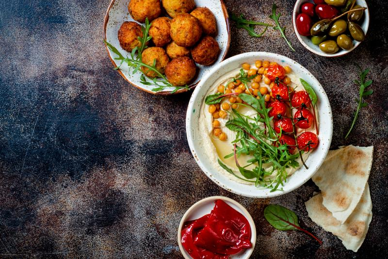 Arabic traditional cuisine. Middle Eastern meze with pita, olives, hummus, stuffed dolma, falafel balls, pickles. royalty free stock image