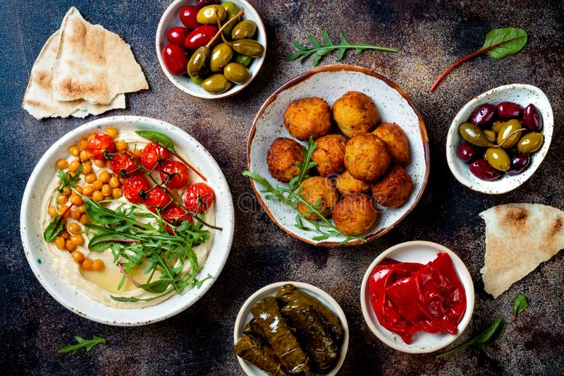 Arabic traditional cuisine. Middle Eastern meze with pita, olives, hummus, stuffed dolma, falafel balls, pickles. stock photo
