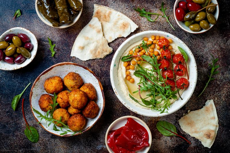 Arabic traditional cuisine. Middle Eastern meze with pita, olives, hummus, stuffed dolma, falafel balls, pickles. stock photography