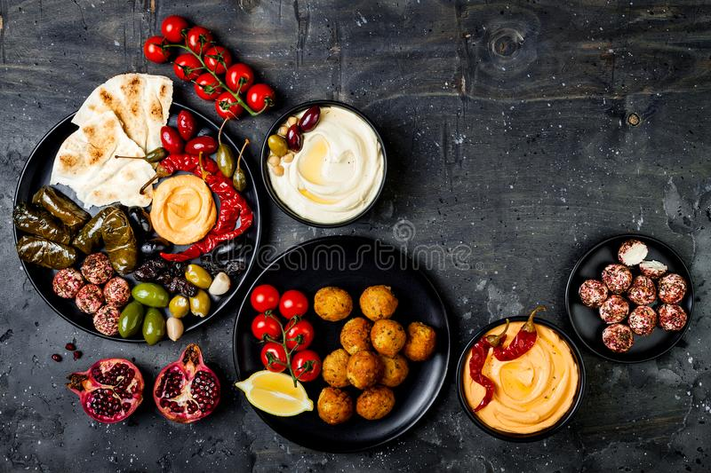 Arabic traditional cuisine. Middle Eastern meze platter with pita, olives, hummus, stuffed dolma, labneh cheese balls, falafel. stock photo