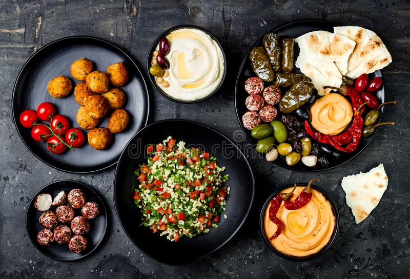 Arabic traditional cuisine. Middle Eastern meze platter with pita, olives, hummus, stuffed dolma, labneh cheese balls, falafel. royalty free stock photos