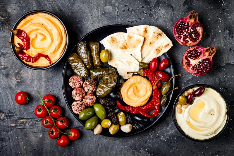 Arabic traditional cuisine. Middle Eastern meze platter with pita, olives, hummus, stuffed dolma, labneh cheese balls in spices. royalty free stock photos