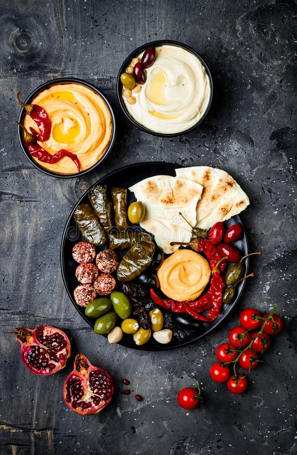 Arabic traditional cuisine. Middle Eastern meze platter with pita, olives, hummus, stuffed dolma, labneh cheese balls in spices. stock images