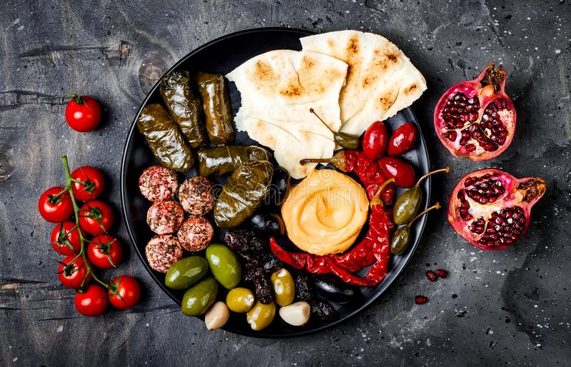 Arabic traditional cuisine. Middle Eastern meze platter with pita, olives, hummus, stuffed dolma, labneh cheese balls in spices. royalty free stock images