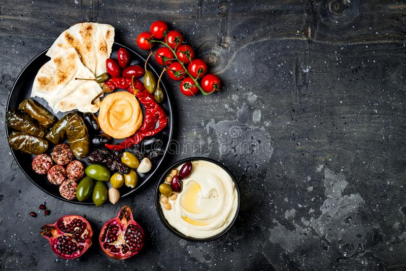 Arabic traditional cuisine. Middle Eastern meze platter with pita, olives, hummus, stuffed dolma, labneh cheese balls in spices. stock photos