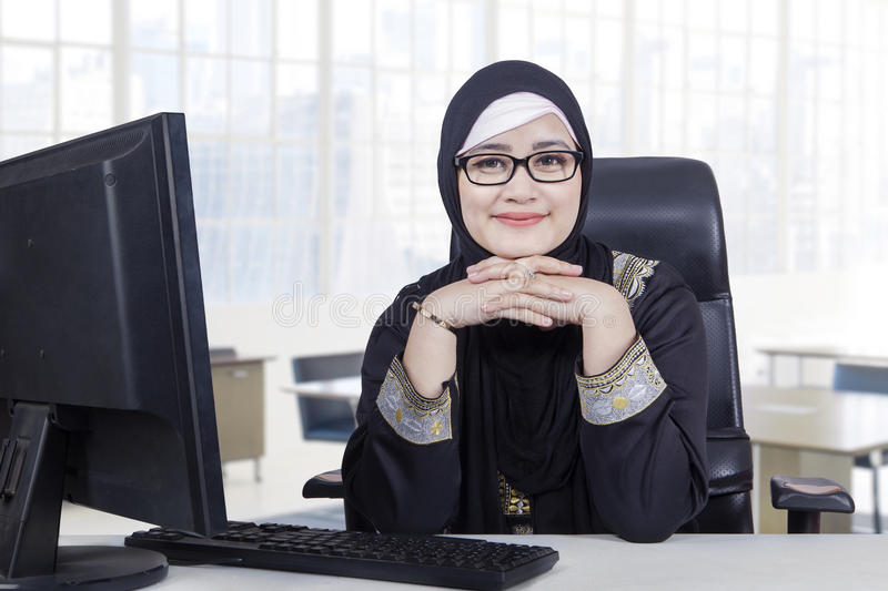 Arabic woman with headscarf smiling in office. Portrait of Arabic young woman working in the office while wearing headscarf and smiling at the camera stock image