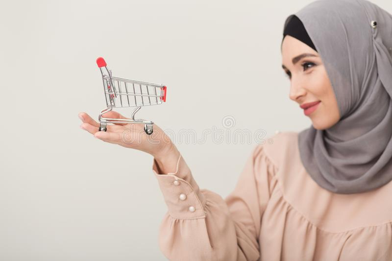 Arabic woman holding shopping cart at studio background stock photography