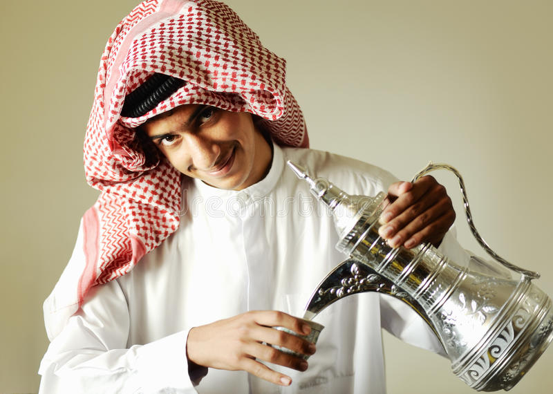 Arabic young man pouring a coffee royalty free stock image