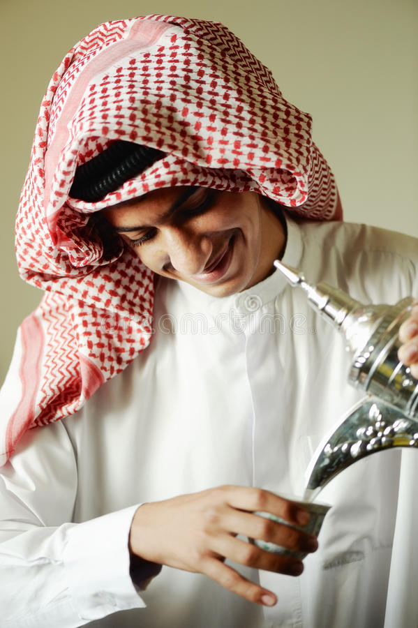 Arabic young man pouring a coffee royalty free stock photos