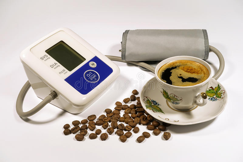 Arabica coffee beans and cup of black coffee, tonometer for meas. Uring blood pressure on a white background stock photography