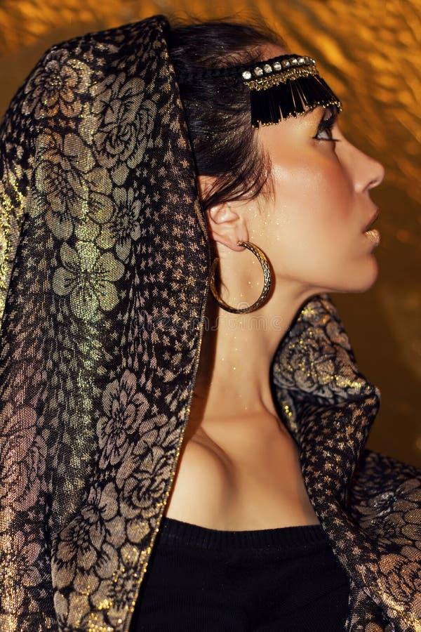 Arabisch vrouwenbrunette in etnische toebehoren, sjaal hijab Gouden samenstelling stock foto's