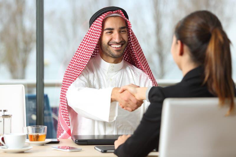 Arabisch zakenman en verkopershandenschudden stock foto's