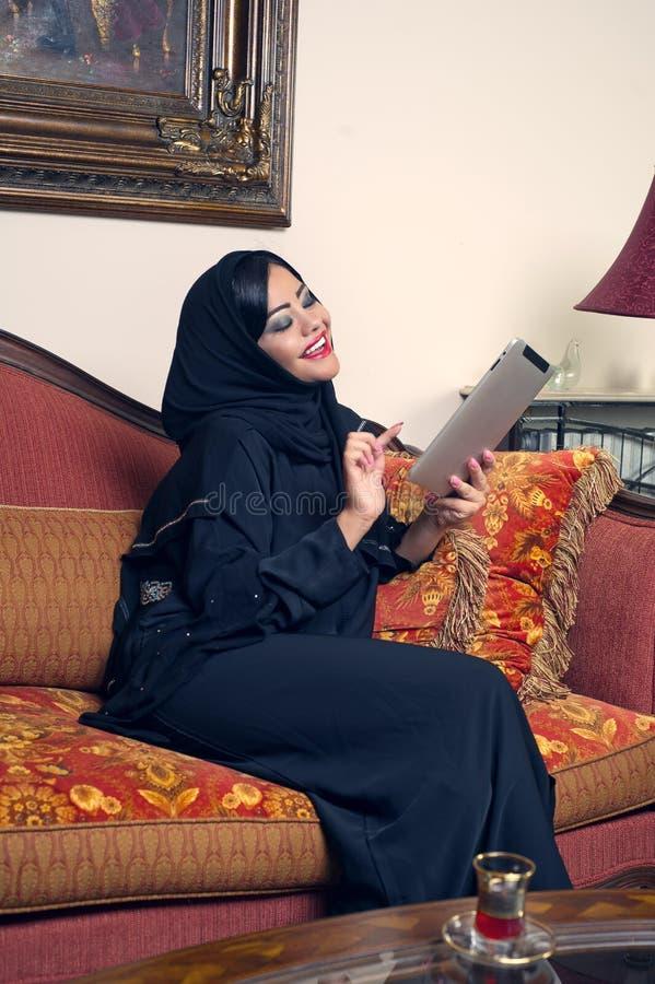 Arabische Dame mit hijab unter Verwendung der Auflage lizenzfreies stockfoto
