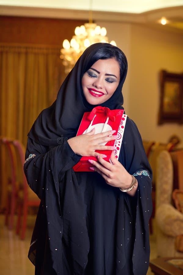 Arabische Dame tragendes hijab, das ein Geschenk empfängt lizenzfreie stockfotografie