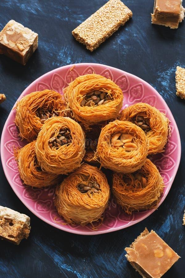 Arabische dessertbaklava, sesambars en sorbet op een blauwe achtergrond Turks Ramadan Dessert Selectieve nadruk Van het Middenoos stock foto
